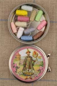Fil Au Chinois round metal tin with 12 pastel tones thread cocoons