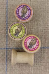 "4 miniature wooden bobbins with ""Au Sajou"" labels"