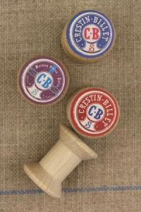 "4 miniature wooden bobbins with ""Crestin-Billet"" labels"