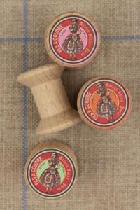 "4 miniature wooden bobbins with ""Fil À l'Indienne"" labels"