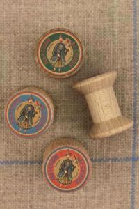 "4 miniature wooden bobbins with ""Fil Au Chinois"" labels"