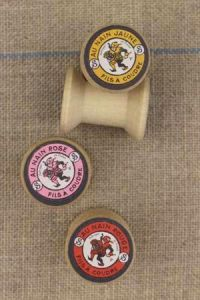 "4 miniature wooden bobbins with ""Fil Au Nain"" labels"