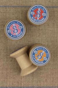 "4 miniature wooden bobbins with ""Sajou"" labels"