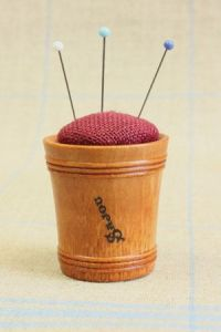 Hornbeam wooden pin cushion covered with dark red linen fabric