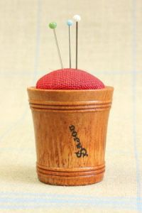 Hornbeam wooden pin cushion covered with red linen fabric